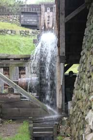 Photo shows water spilling as it drives a water wheel at an old blacksmithing shop in Massachusetts.