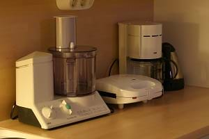 A variety of electrical kitchen appliances that inlcude a mixer, a coffee maker and a sandwich maker.
