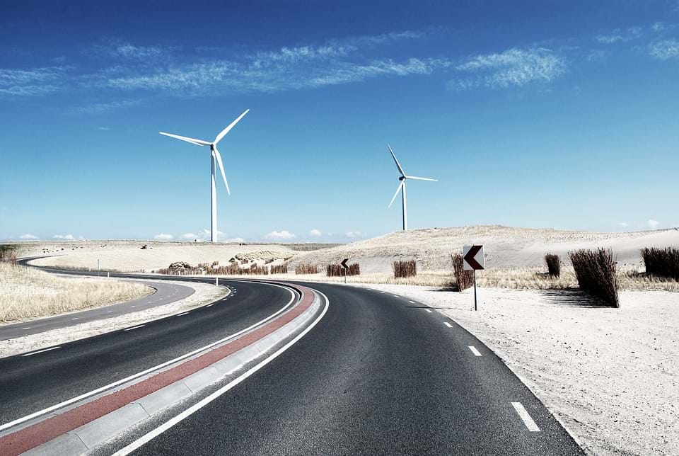 A photo of a winding road with two white windmills.