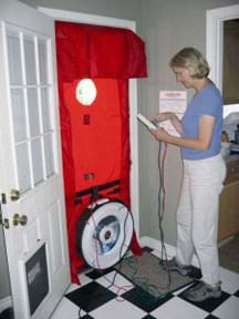 Photo shows a woman standing by a front door where a blower door test is installed for a home energy audit.
