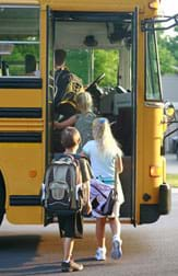 Photo shows four young students climbing onto a school bus.
