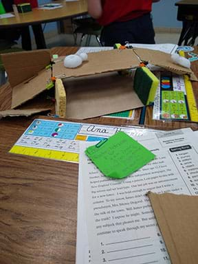 A student gluing sponges to cardboard to create bridge and underpass.