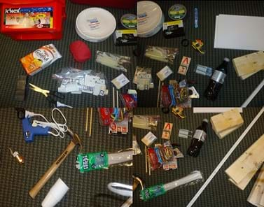 Four photos show a range of materials and tools lying on the floor: red box of K'NEX components, paper plates, goldfish crackers, yarn, glue gun and glue sticks, nails, duct tape, candies, scotch tape, paper, boards, corner edging, soda pop, mouse traps, toothpicks, staple gun, staples, dominoes, scissors, magnets, pipe cleaners, hammer, pulley, toy car, cups, screws, small dowels, rubber bands and marbles.