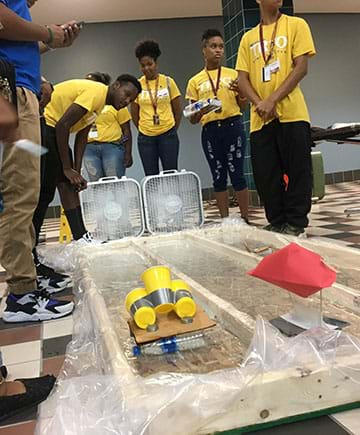 Students stand around two classroom-made water channels and watch their boats race to the opposite end. Two fans propel the boats down each channel.