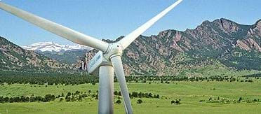 Photo shows a three-bladed wind turbine with a backdrop of mountains.