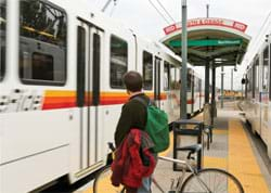 Photo shows a man with a backpack and bicycle waiting at a light rail train station.
