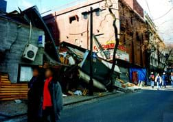 A photograph shows a collapsed multi-story building.