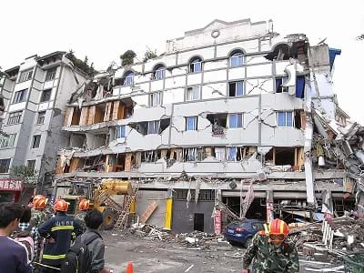 A photograph shows emergency first responders in gear and helmets in front of a six-story residential building (now looks like five-stories) that looks broken, cracked and crumbling.