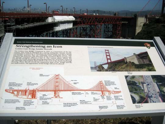 "A photograph of a National Park Service sign near the under-construction steel truss and concrete north end of the Golden Gate Bridge in San Francisco. The sign title is ""Strengthening an Icon: Golden Gate Bridge Seismic Retrofit,"" and it shows two photographs and a labeled side-view diagram of the full bridge."