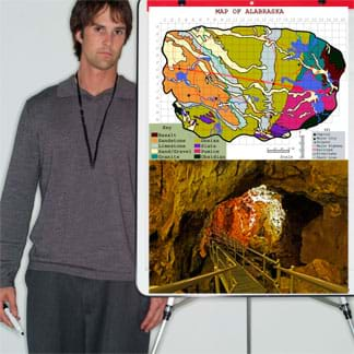 Photo shows a young man standing by an easel with a map and a cavern photo on it.
