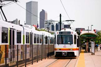 Photo shows two electric light-rail trains at a station, with the skyscrapers of the Denver skyline in the background.