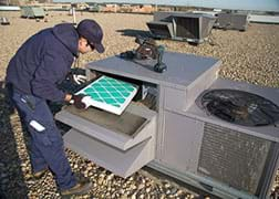 A photograph shows a technician inspecting the filter on a rooftop air conditioning unit.