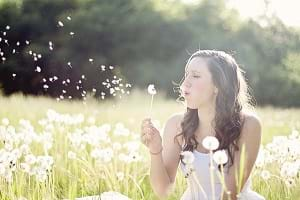 A girl blowing a dandelion in the grass.