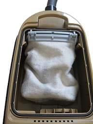 A photograph shows the back of an upright vacuum cleaner with the plastic cover removed so that the soft, fabric cleaner bag is shown.