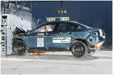 A photograph shows a sedan automobile after an indoor crash test with its front end crumpled where it hit a wall head on.