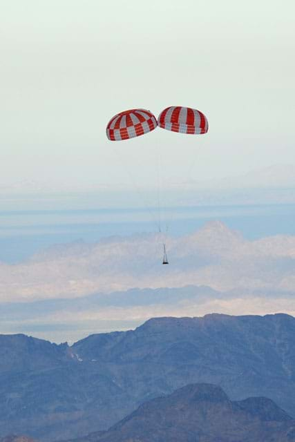A photograph shows a NASA robot floating to the ground, slowed by a double parachute.