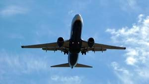 A photograph from the ground looking up at an airplane descending to land at Murcia San Javier airport in Spain.