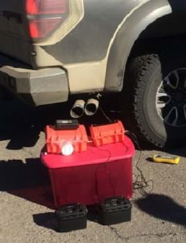 A photograph shows two monitors in red plastic tackle box-sized containers, powered by batteries, placed on top of a plastic tub container about a foot off the ground so that they are near a pickup truck's dual tailpipes.
