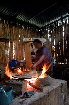 A photograph shows a person cooking tortillas (flatbread) indoors over a wood-fired three-stone stove, essentially an open fire.