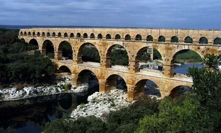 "A photograph shows the Roman aqueduct ""Pont du Gard"" in southern France. It's a three-layered, multi-arched masonry structure with different-sized arches on each level."