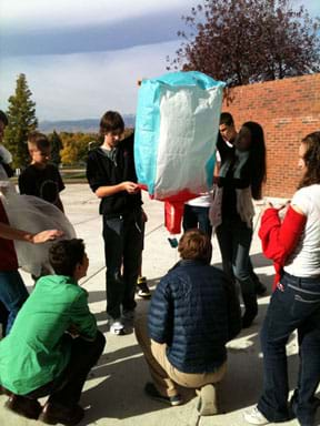 Photo shows 10 students outside, holding a square-shaped green, red and white tissue-paper balloon.
