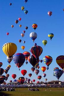Photo shows more than 50 colorful hot air balloons rising from a field into the blue sky.