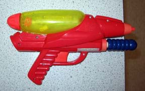 Photo shows a red gun-shaped toy laying flat on a table with its nozzle pointed off the table edge.