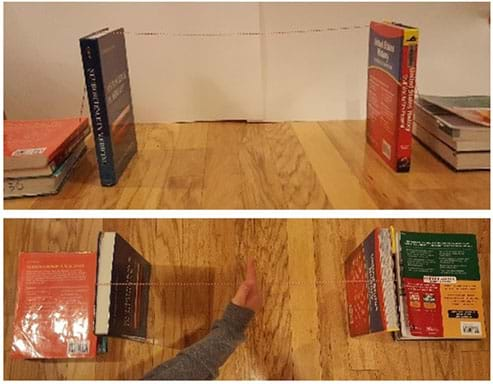 Two photographs: A side view shows two text books standing up vertically about 18 inches apart, with one long string tied around one book, strung across the gap and then tied around the second book. To the outer side of each standing textbook, a pile of three textbooks puts weight on the tail ends of the strings (anchorages). A view from above of the same setup shows a hand pressing down on the middle of the string across the gap between the two books, which does not result in the books falling inwards.