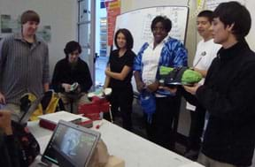 Photo shows six students at the front of a class with their varied shoe prototypes.
