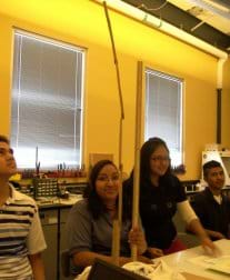 In a classroom, four students measure the height of a paper structure stretching from a table top to the ceiling.
