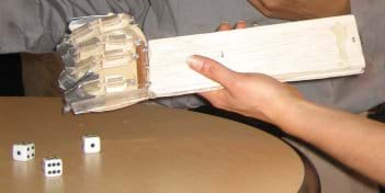 Photo shows a board for a forearm, and eyelet screws, fishing line, plastic tubing and duct tape combined to make a crude hand with fingers, along with dice at a table.