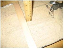 Photo shows a ruler placed vertically into the bottom of the furrow next to another ruler placed across the pan of sand, resting on the pan edges, providing a consistent level to which the depth can be measured.