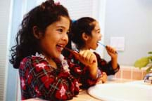 Photo shows two young girls brushing their teeth over a sink.