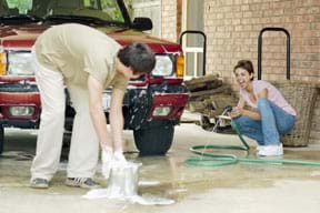Photo shows two people washing a car.