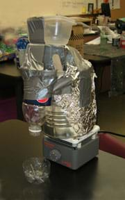 Photo shows a contraption made from a large tin can, plastic bottles and containers, aluminum foil and duct tape, sitting on a hot plate.
