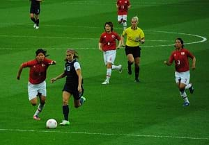 A photograph shows a green grassy soccer field with the U.S. women's team playing against the Japanese women's team. Seven players chase a white ball.