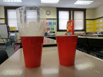 Photo shows two red cups, one with an upside-down top half of a two liter bottle containing a coffee filter resting inside of it.