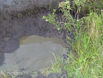Photo shows a hole in the ground filled with dirty, still water.