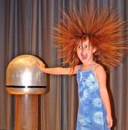 A young girl placing her hand on a Van de Graaff generator causing her hair to rise