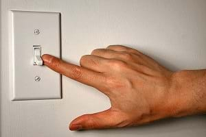 A man placing his finger on an on/off electrical wall switch.