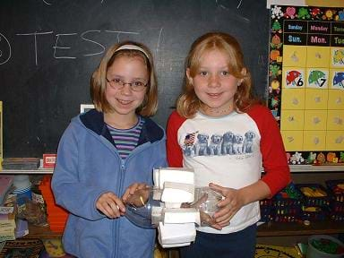 A photograph shows two girls holding a clear plastic two-liter botttle with box-shaped fins attached around its middle section.