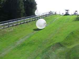 Zorbing, which shows a large ball rolling down a hill.