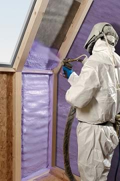 A man in white coveralls, gloves and a face mask sprays purple WALLTITE polyurethane spray foam insulation between the wooden stud framing of the walls of a house.