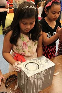 A photograph shows two young girls working with a speaker on a table; the speaker cone is covered with oobleck, a drippy white goo, as are their hands.