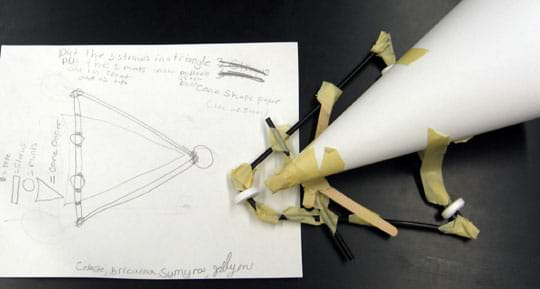 Photo shows a piece of paper with pencil sketches and words next to a vehicle chassis made from black straws, mint candies (wheels), popsicle sticks and tape, with a conical-shaped paper sail.
