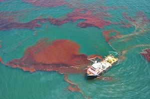 A photo shows a NOAA response and restoration boat near brown gunky masses in the green waters of the Gulf of Mexico from the Deepwater Horizon oil spill.
