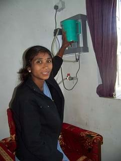 A photo shows a female health aide using a water filter mounted to the wall in a room.