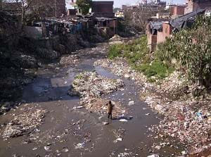 A polluted rubbish-laden river surrounded by slum shacks and trash in the Indian Himalayas.