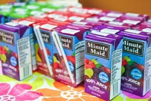 A photograph shows ~20 single-serving rectangular Minute Maid juice boxes with attached straws on a table top.
