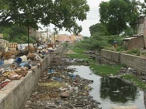 A polluted canal in India overflowing with garbage.